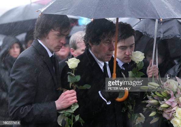 The sons of convicted Old Bailey bomber Dolours Price Danny and Oscar stand with her exhusband Stephen Rea at Milltown cemetary in Belfast Northern...