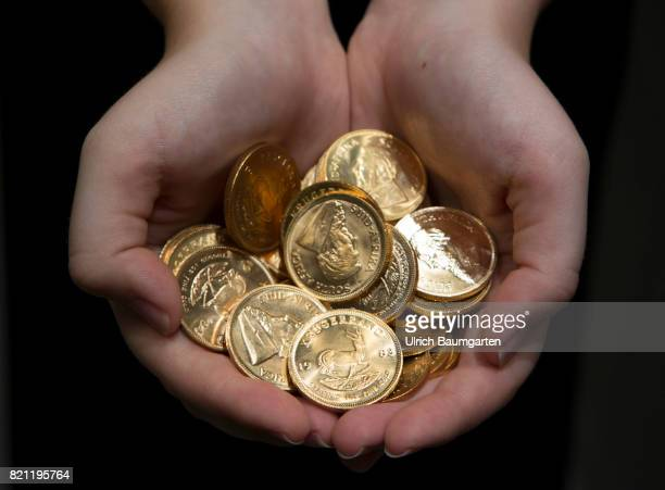 The South African Krugerrand the most famous gold coin in the world celebrates its 50th anniversary in 2017 The photo shows hands with Krugerrand...