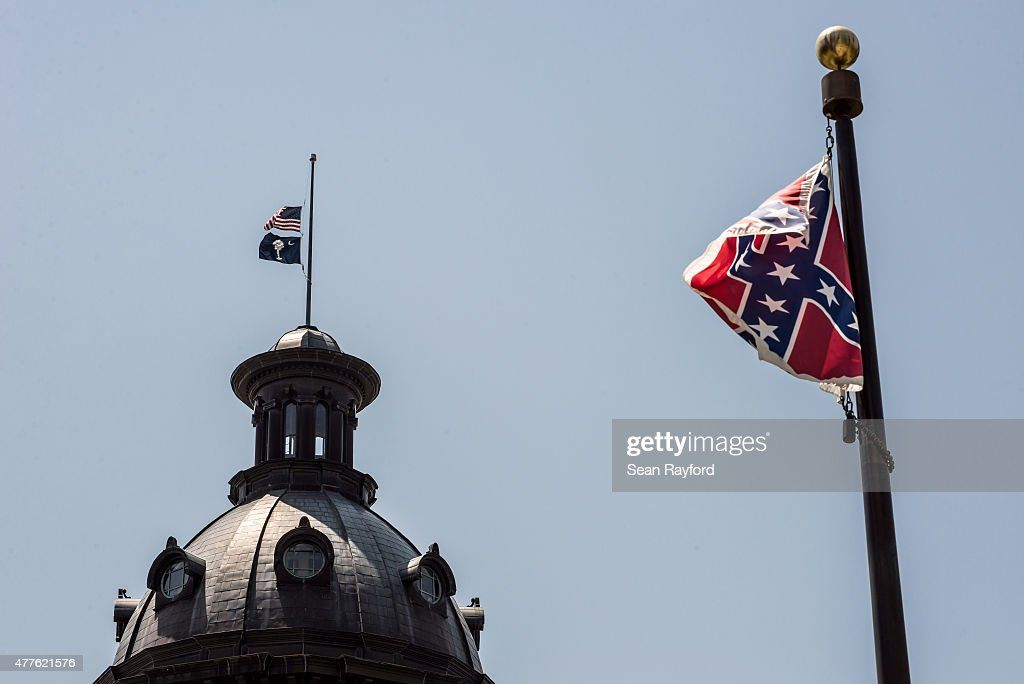 The South Carolina and American flags fly at half mast as the Confederate flag unfurls below at the Confederate Monument June 18 2015 in Columbia...