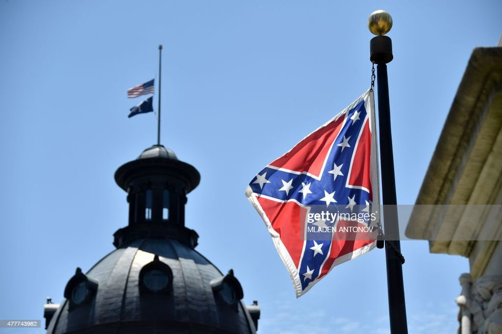 The South Carolina and American flags flying at halfstaff behind the Confederate flag erected in front of the State Congress building in Columbia...