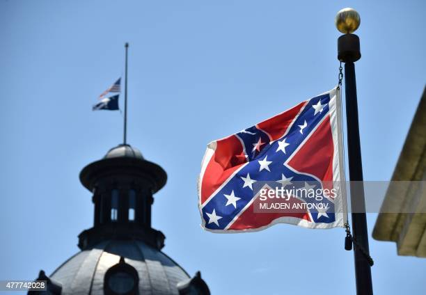The South Carolina and US flags are seen flying at halfstaff behind the Confederate flag erected in front of the State Congress building in Columbia...