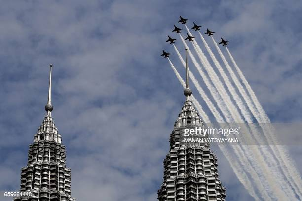 TOPSHOT The South Korean Air Force 'Black Eagles' aerobatic team flies past Malaysia's Petronas Twin Towers in Kuala Lumpur on March 29 2017 / AFP...