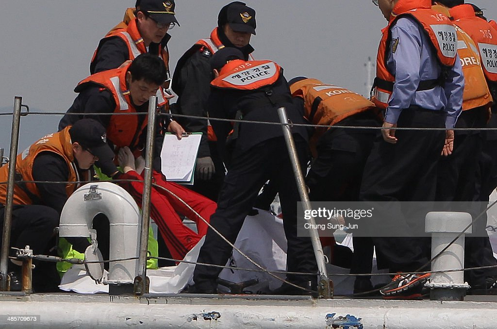 The South Korean coast guard carry a victim of the sunken ferry at the site of the ferry off the coast of Jindo Island on April 20, 2014 in Jindo-gun, South Korea. At least forty six people are reported dead, with 256 still missing. The ferry identified as the Sewol was carrying about 470 passengers, including the students and teachers, traveling to Jeju Island.
