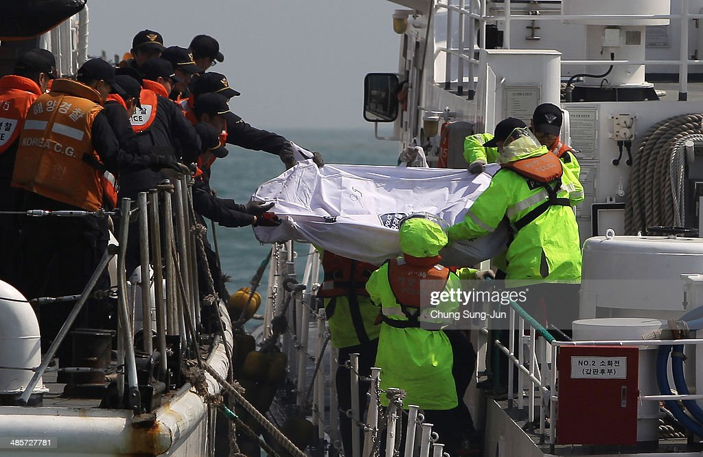The South Korean coast guard carry a victim of the sunken ferry at the site of the ferry off the coast of Jindo Island on April 20, 2014 in Jindo-gun, South Korea. At least fifty six people are reported dead, with 246 still missing. The ferry identified as the Sewol was carrying about 470 passengers, including the students and teachers, traveling to Jeju Island.