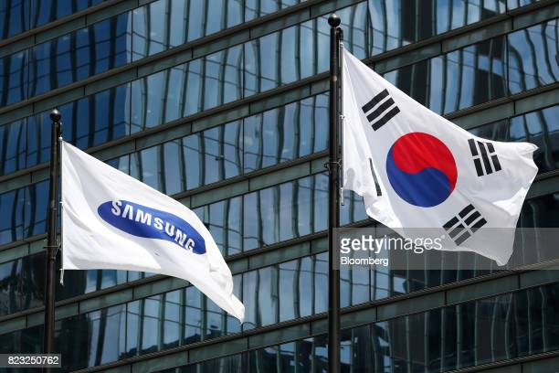 The South Korean national flag right and the Samsung Electronics Co corporate flag fly outside the company's Seocho office building in Seoul South...