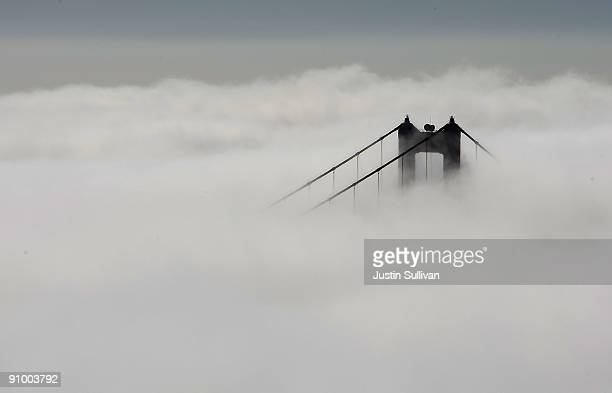 The south tower of the Golden Gate Bridge peeks out from a blanket of fog September 21 2009 in the Marin Headlands of Sausalito California After a...