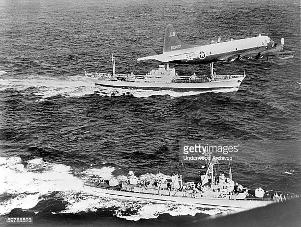 The Soviet freighter Anosov rear being escorted by a Navy plane and the destroyer USS Barry while it leaves Cuba probably loaded with missiles under...