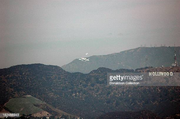 The space shuttle Endeavour atop of NASA's modified Boeing 747 Shuttle Carrier Aircraft escorted by two fighter jets flies by the Hollywood sign...