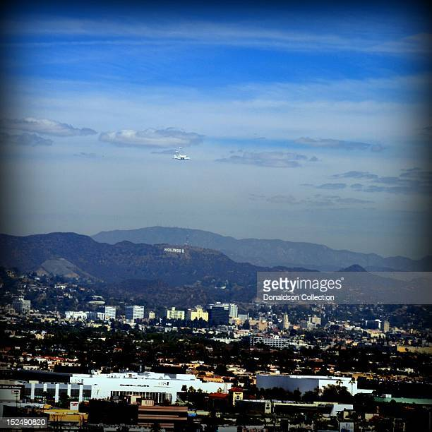 The space shuttle Endeavour atop of NASA's modified Boeing 747 Shuttle Carrier Aircraft escorted by two fighter jets flies over the Hollywood Sign...