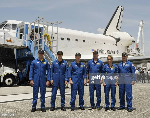 The space shuttle Endeavour crew pose by the orbiter after landing July 31 2009 at Kennedy Space Center in Florida at the end of a 16day mission to...