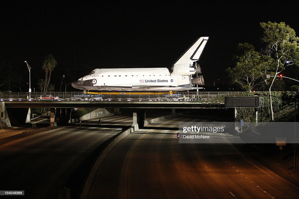 The space shuttle Endeavour crosses over the 405 freeway as it is transported from Los Angeles International Airport (LAX) to the California Science Center in Exposition Park where it will be on permanent public display on October 12, 2012 in Los Angeles, California. Endeavour was flown cross-country atop NASA's Shuttle Carrier Aircraft from Kennedy Space Center in Florida to LAX on its last flight ever on September 21. Completed in 1991, Endeavour was built to replace the space shuttle Challenger which disintegrated during a catastrophic re-entry accident. This fifth and final space shuttle orbiter circled the earth 4,671 times and traveled nearly 123 million miles during its 25 missions from 1992 to 2011.