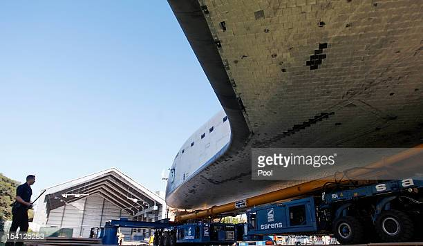 The Space Shuttle Endeavour is guarded by a lone LAPD officer as it sits outside its temporary hangar at the California Science Center on October 14...