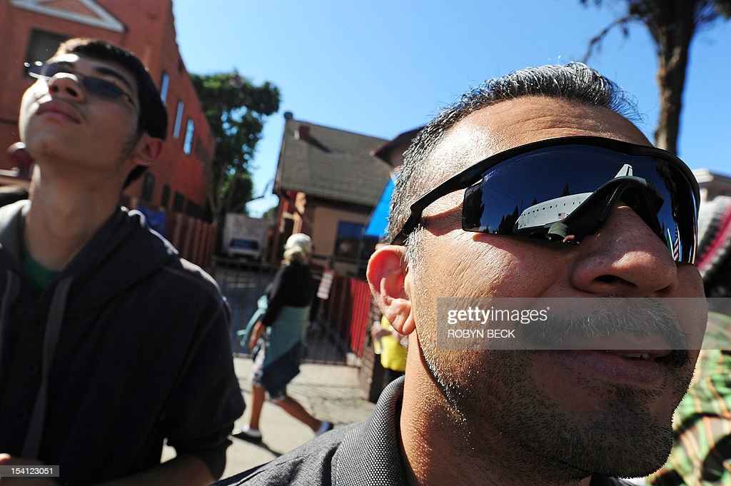 The Space Shuttle Endeavour is reflected in the sunglasses of spectator Ever Hernandez as it nears the end of its journey to the California Science Center in Exposition Park in Los Angeles October 14, 2012. The 170,000-pound (77,272 kg) shuttle completed its 12-mile (19km) road trip from Los Angeles International Airport to its permanent museum home just over 18 hours late. AFP PHOTO / Robyn Beck