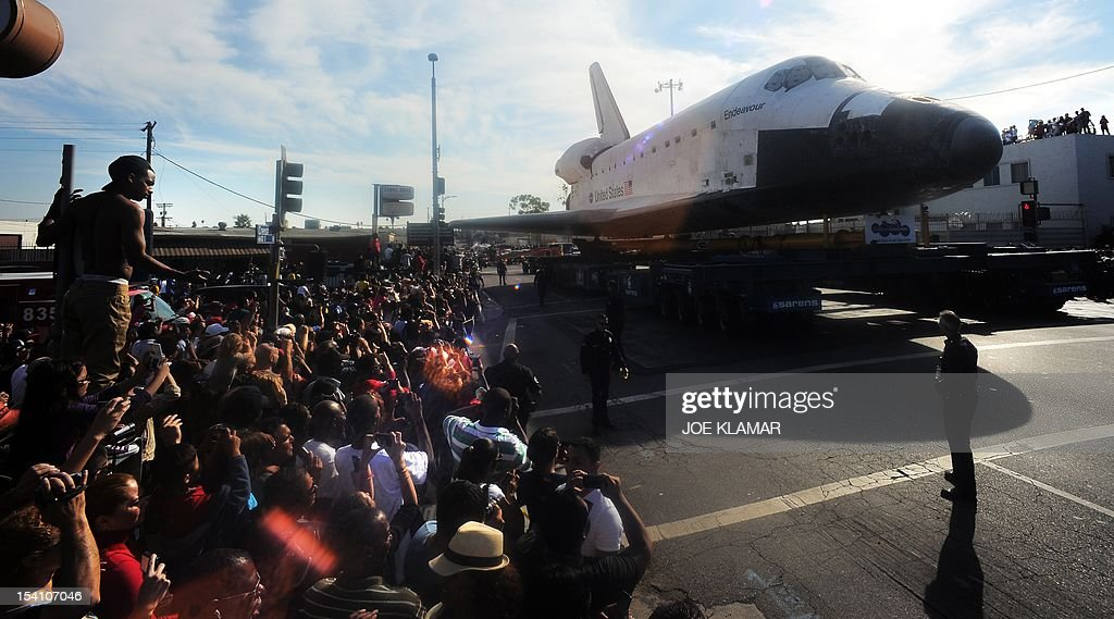 The Space Shuttle Endeavour is transported through the streets of Los Angeles on its final journey to its permanent museum home on October 13, 2012 in Inglewood, California. The 170,000-pound (77,272 kg) shuttle will travel at no more than 2 mph (3.2 km per hour) along a 12-mile (19km) route from Los Angeles International Airport (LAX) to its final home at the California Science Center. NASA's space shuttle program ended in 2011 after 30 years and 135 missions.