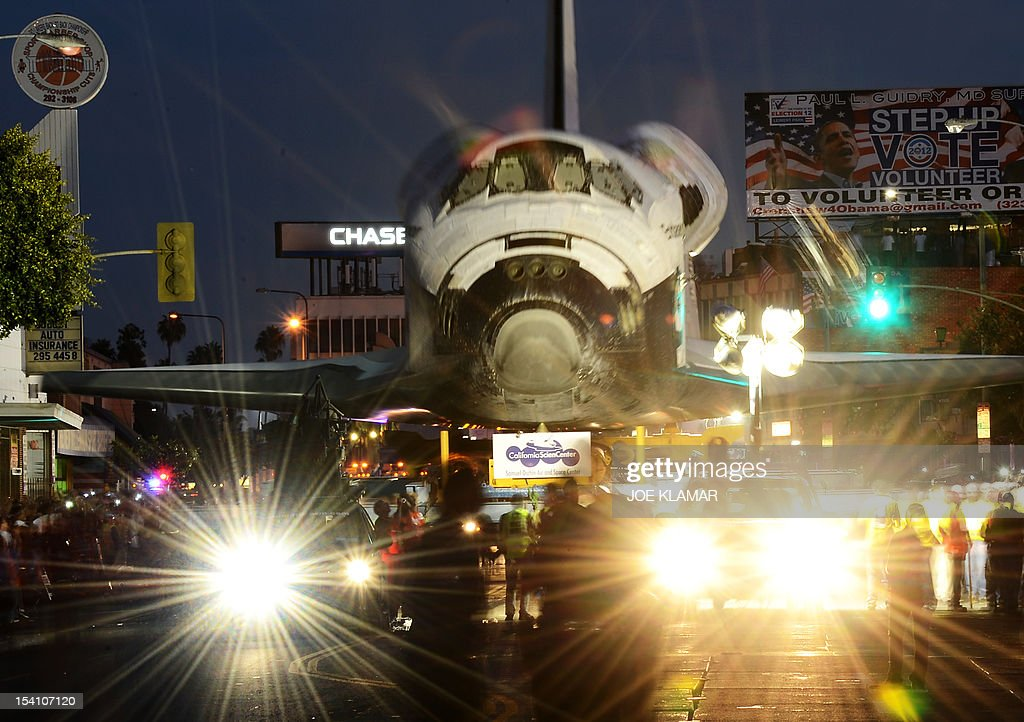 The Space Shuttle Endeavour is transported through the streets of Los Angeles on its final journey to its permanent museum home on October 13, 2012 in Inglewood, California. The 170,000-pound (77,272 kg) shuttle will travel at no more than 2 mph (3.2 km per hour) along a 12-mile (19km) route from Los Angeles International Airport (LAX) to its final home at the California Science Center. NASA's space shuttle program ended in 2011 after 30 years and 135 missions. AFP PHOTO/JOE KLAMAR