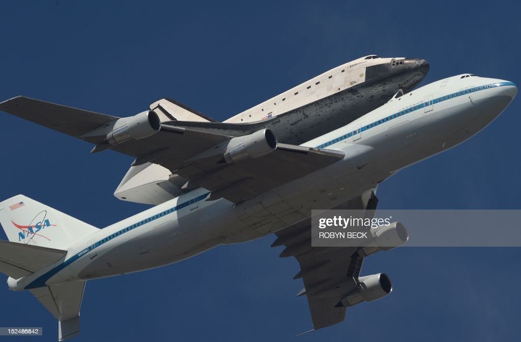The Space Shuttle Endeavour, mounted atop NASA's modified Boeing 747, flies over Hollywood, California on its final flight, September 21, 2012. The retired space shuttle is spending it's last day in the air on a 5-hour flyover before landing at the Los Angeles International Airport, where it will stay for a few weeks before taking a slow-speed land journey across town through neighborhoods to its final museum home, the California Space Center. AFP PHOTO / Robyn Beck / AFP / ROBYN