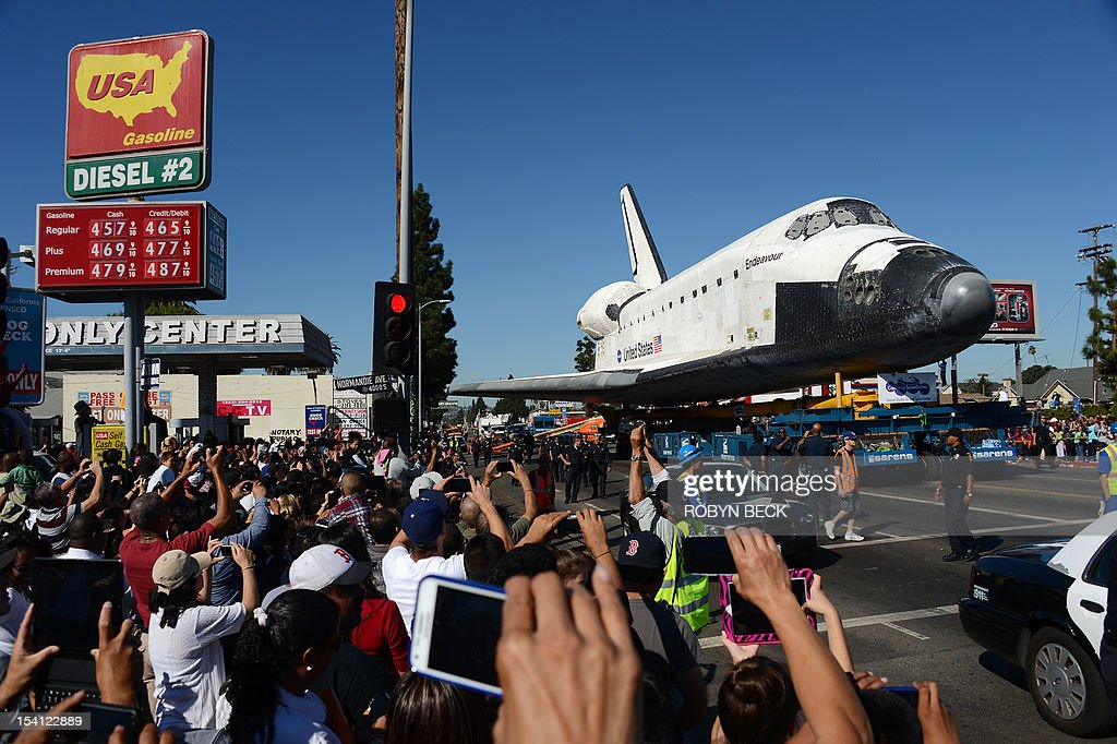 The Space Shuttle Endeavour passes a gas station as it nears the end of its journey to the California Science Center in Exposition Park in Los Angeles October 14, 2012. The 170,000-pound (77,272 kg) shuttle completed its 12-mile (19km) road trip from Los Angeles International Airport to its permanent museum home just over 18 hours late. AFP PHOTO / Robyn Beck