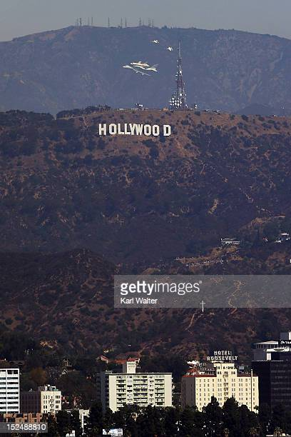 The space shuttle Endeavour sitting on top of NASA's Shuttle Carrier Aircraft or SCA flies near the Hollywood sign on September 21 2012 in Los...