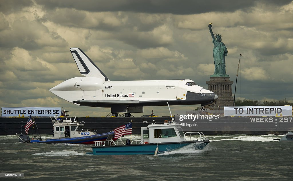 The space shuttle Enterprise is brought past the Statue of Liberty on a barge on June 6, 2012 in New York City. The shuttle is on it's way to the USS Intrepid, where it be on display for viewing by the general public. NASA's space shuttle program came to an end in August, 2011, after 30 years of service.