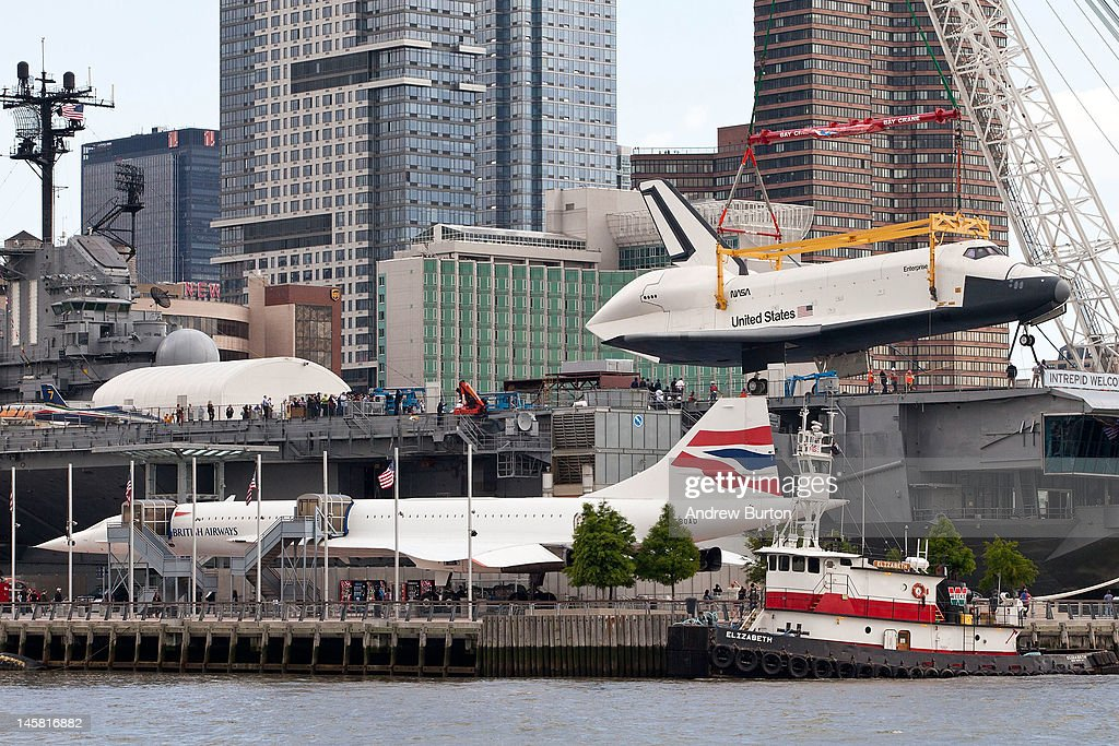 The space shuttle Enterprise is lifted by a crane on to the USS Intrepid on June 6, 2012 in New York City. NASA's space shuttle program came to an end in August, 2011, after 30 years of service. Upon the Intrepid, the space shuttle be on display for viewing by the general public. The British Airways Concorde is seen in the foreground.