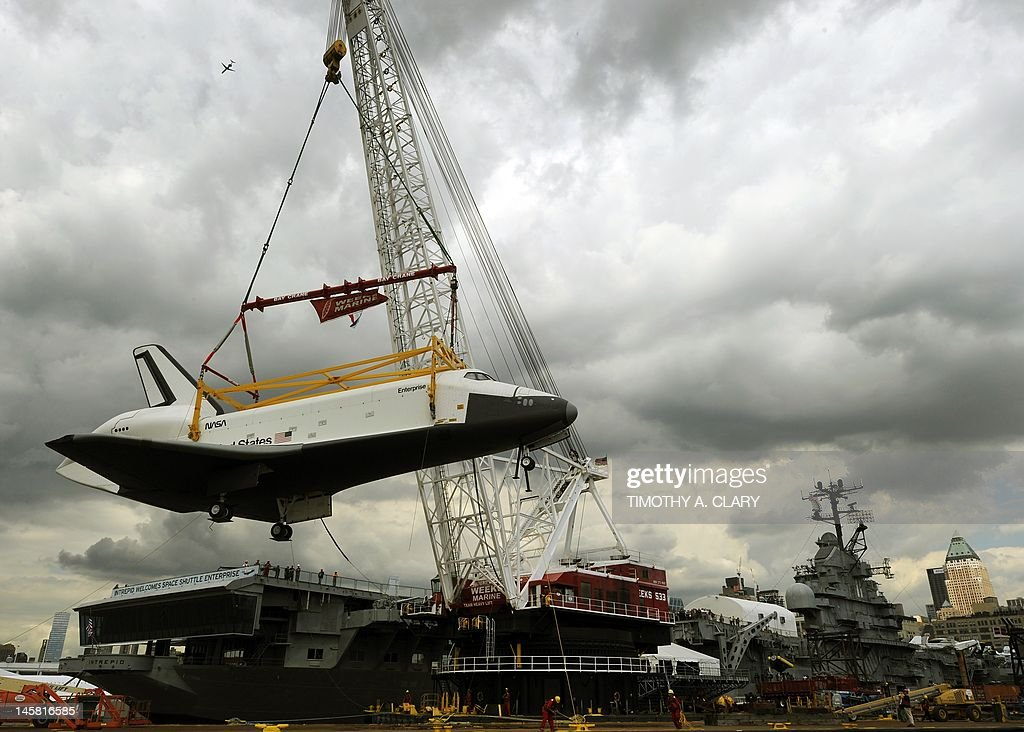 The space shuttle Enterprise is lifted from the barge to the flight deck in New York on June 6, 2012 as it arrives at the USS Intrepid Sea, Air and Space Museum where it will be permanently displayed.