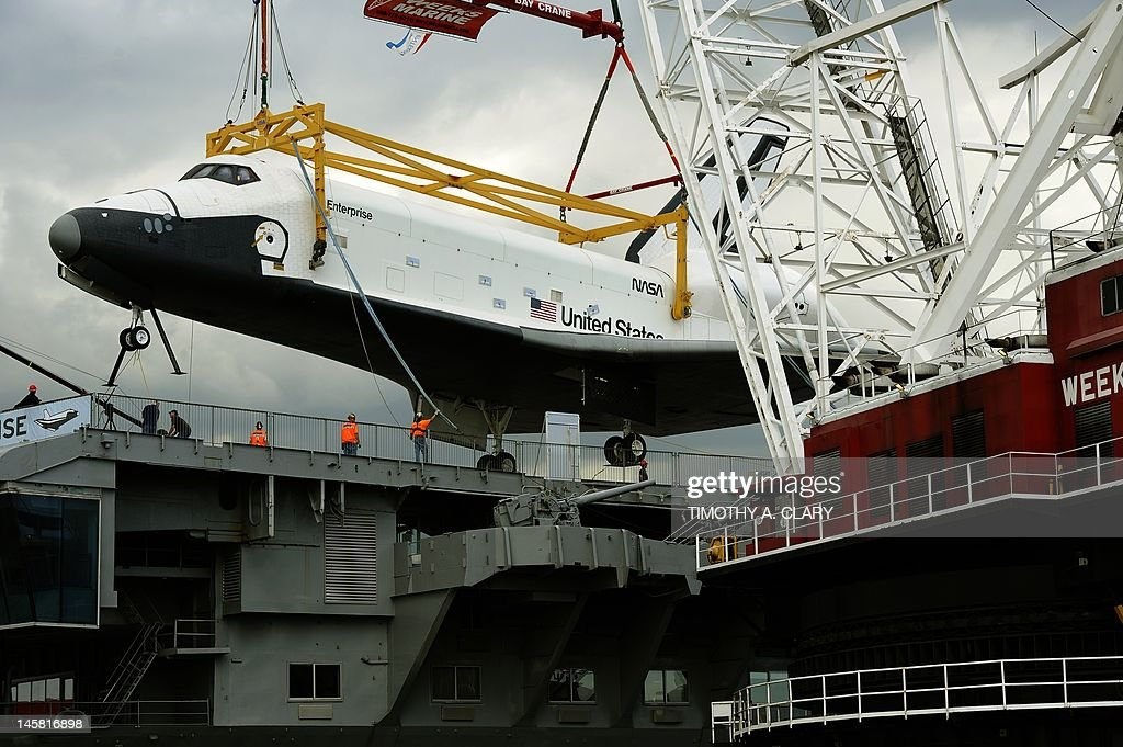 The space shuttle Enterprise is lifted from the barge to the flight deck New York June 6, 2012 as it arrives at the Intrepid Sea, Air and Space Museum where it will be permanently displayed.