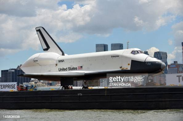 The space shuttle Enterprise is towed by barge in New York June 6 2012 on its way to the Intrepid Sea Air and Space Museum where it will be...
