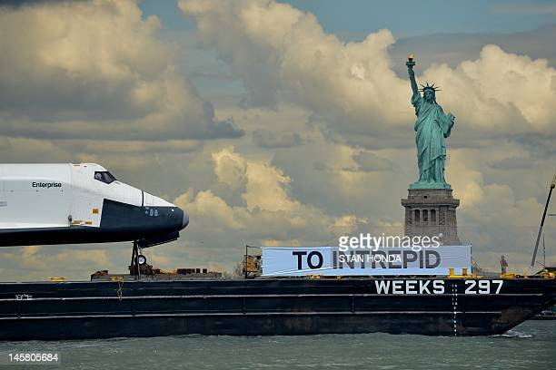 The space shuttle Enterprise is towed by barge past the Statue of Liberty in New York June 6 2012 on its way to the Intrepid Sea Air and Space Museum...