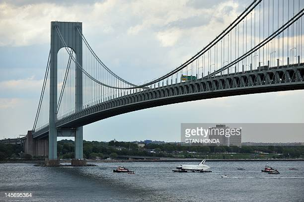 The space shuttle Enterprise is towed by barge under the Verrazano Bridge June 3 2012 in New York on its way to dock in Port Elizabeth New Jersey...