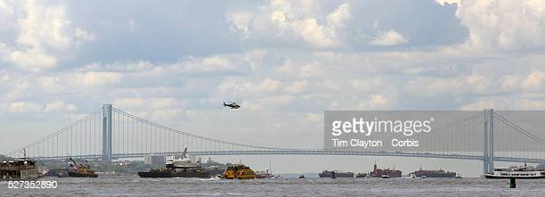 The Space Shuttle Enterprise passes lower Manhattan on a barge along the Hudson River as it completes her journey to the Intrepid Sea Air and Space...
