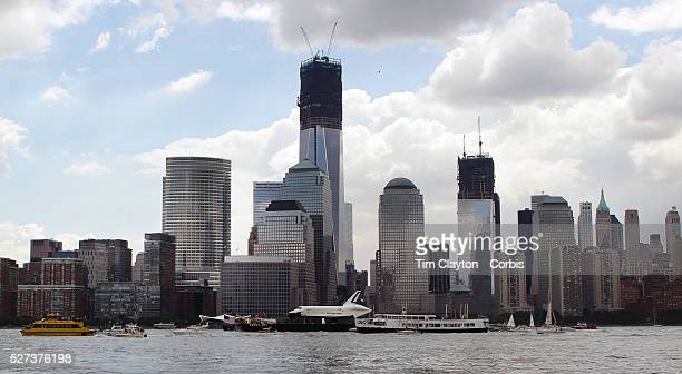 The Space Shuttle Enterprise passes the One World Trade Centre and lower Manhattan on a barge along the Hudson River as it completes her journey to...