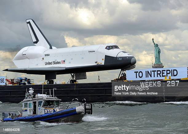 The Space Shuttle Enterprise passes the Statue of Liberty as it is towed by barge along the Hudson River from Weeks Marina in New Jersey to it's new...