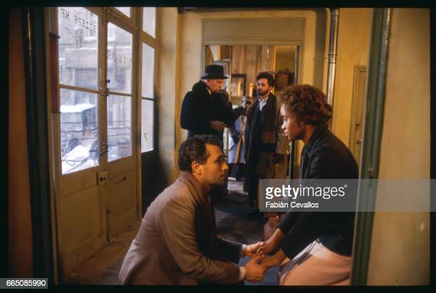 The Spanish opera singer Jose Carreras crouches as he hold hands with American opera singer Barbara Hendricks in a corridor as Italian actors Massimo...