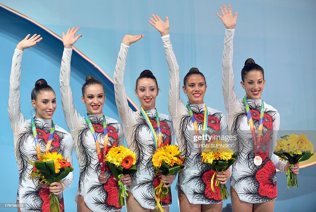 The Spanish team waves on the podium after winning bronze in the three balls two ribbons final during the 32nd Rhythmic Gymnastics World Championships in Kiev on September 1, 2013. AFP PHOTO / SERGEI SUPINSKY