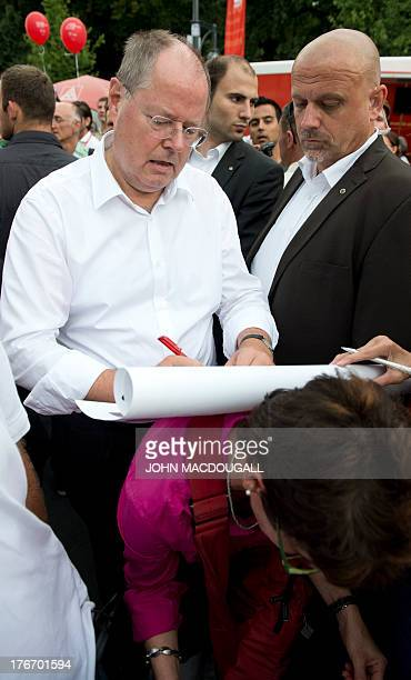 The SPD's main candidate in upcoming parliamentary elections Peer Steinbrueck autographs a poster on the back of a wellwisher during a walkabout at...