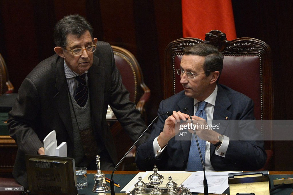 The speaker of the parliament, Gianfranco Fini (R) chats with minister Piero Giarda prior a session on a key budget vote on December 21, 2012 in Rome. The Italian parliament prepared Friday for a key budget vote which will trigger the resignation of Prime Minister Mario Monti, who is expected to reveal this weekend whether he will run in the upcoming election. AFP PHOTO / ALBERTO PIZZOLI