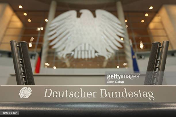 The speaker's podium stands under the Federal Eagle in the plenary hall of the Bundestag on October 17 2013 in Berlin Germany Workers installed new...