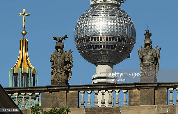 The sphere of the broadcast tower at Alexanderplatz and the cross on top of the Dom cathedral stand behind statues on the Deutsche Historisches...