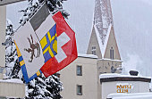 The spire of the church of St Johann and the flags of the Canton of Graubuenden and Switzerland seen in the village of Davos Switzerland Sunday...