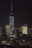 The spire of the One World Trade Center the tallest building in the Western Hemisphere glows green for the Seattle Seahawks and alternately orange...