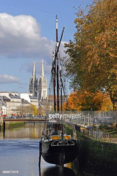 The spires of the cathedral 'Saint Corentin' and old sailing ships alongside the quay on the Odet river in autumn in Quimper
