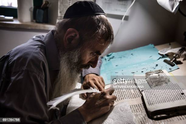The spokesman for the Jewish community in Hebron Noam Arnon writes a Torah scroll at the renovated 16th century Abraham Avinu Synagogue in the...