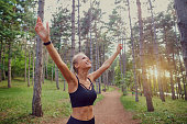 The sports girl  her hands up in the forest. Concept of victory motivation in sports.