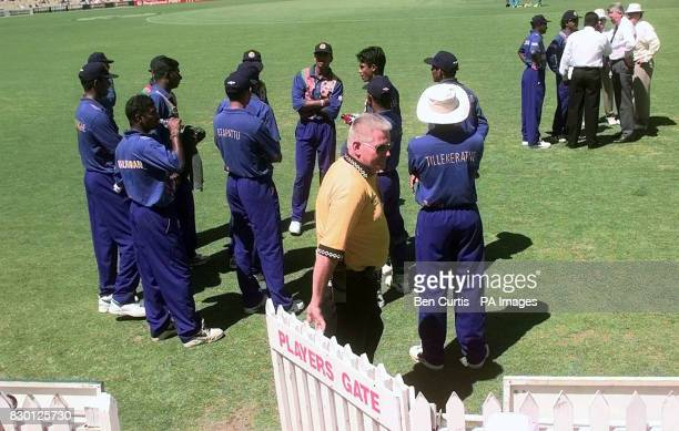 The Sri Lankan team wait as captain Arjuna Ranatunga tries to resolve matters after bowler Muttiah Muralitharan was called for chucking by umpire...