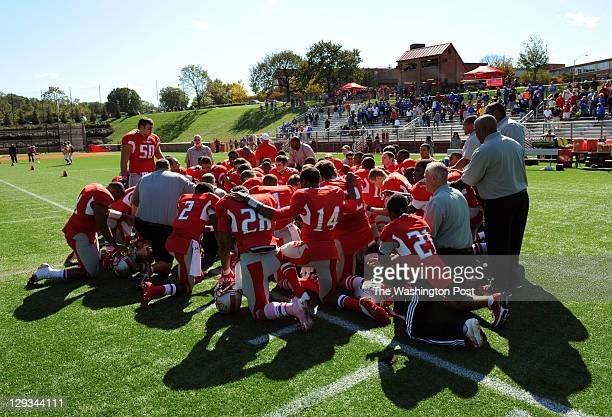 The St John's team kneels in prayer before the game against DeMtaha at St John's College High School on Saturday October 15 2011 DeMatha defeated St...