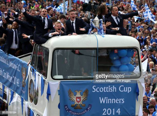 The St Johnstone team make their way through the crowds on an open top bus during the Scottish Cup winners parade in Perth