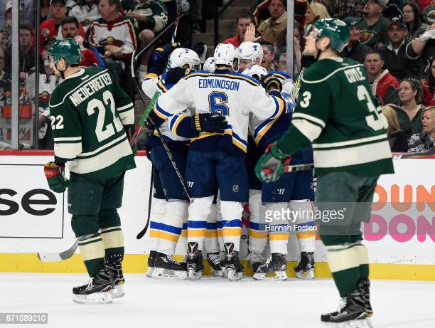 The St Louis Blues celebrate a goal by Alexander Steen as Nino Niederreiter and Charlie Coyle of the Minnesota Wild skate past during the first...
