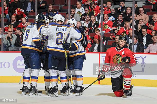 The St Louis Blues celebrate after scoring and tying the game as Brent Seabrook of the Chicago Blackhawks kneels to the side in the second period of...