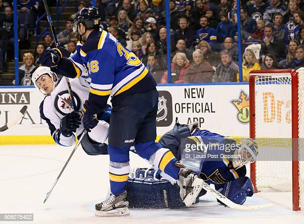 The St Louis Blues' Troy Brouwer middle knocks down the Winnipeg Jets' Alexander Burmistrov in front of Blues goaltender Brian Elliott in the second...