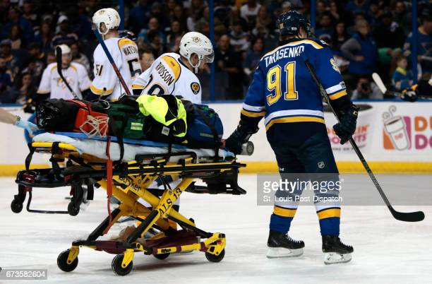 The St Louis Blues' Vladimir Tarasenko joins the Nashville Predators' Viktor Arvidsson as they bring a stretcher for Nashville's Kevin Fiala who was...